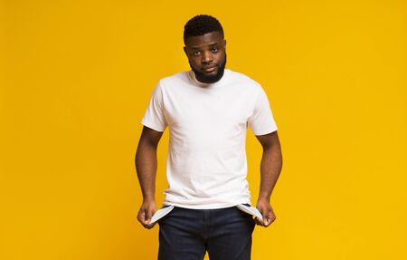 Poverty and absence of money. Unemployed sad african american man showing empty pockets, yellow studio background