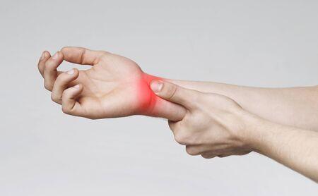 Millennials Krankheit. Junger Mann, der an Karpaltunnelsyndrom leidet, schmerzhaftes Handgelenk berührt, Panorama Standard-Bild