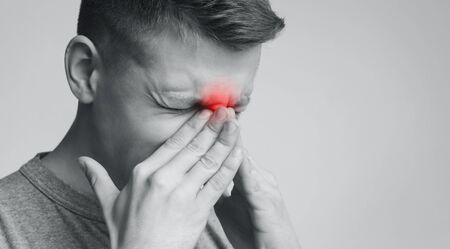 Frustrated man suffering from sinus pressure, touching his nose with closed eyes, free space Stock Photo