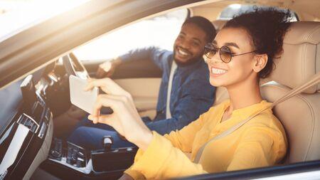 Feliz pareja afroamericana tomando selfie en coche, conduciendo a un nuevo destino, espacio libre