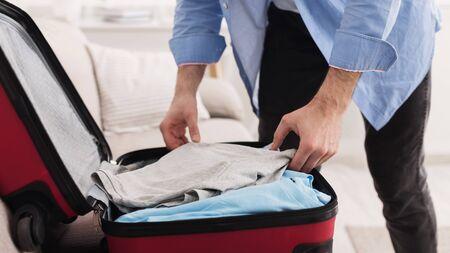 Prepare for business trip. Businessman packing clothes into travel bag, closeup Stock Photo