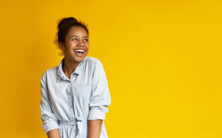 Excited african american girl looking upwards standing against yellow studio background, free space