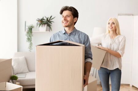 House Moving. Cheerful Man And Woman Carrying Boxes Into New Apartment, Empty Space