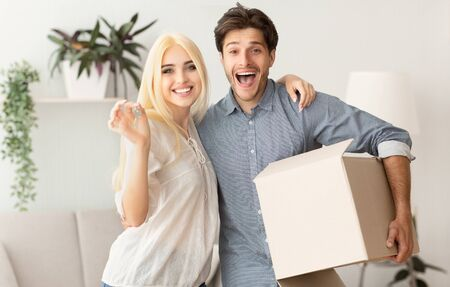 New House Owners. Loving Couple Hugging Holding Key And Moving Box. Free Space
