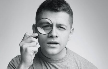 Young suspicious man looking at camera through magnifier, black and white photo