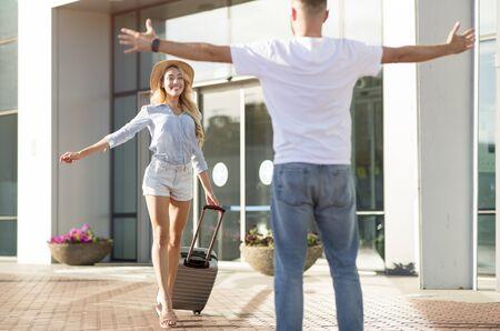 Ragazzo che va a prendere la sua ragazza all'aeroporto, dando il benvenuto a casa dallo studio o dal lavoro all'estero