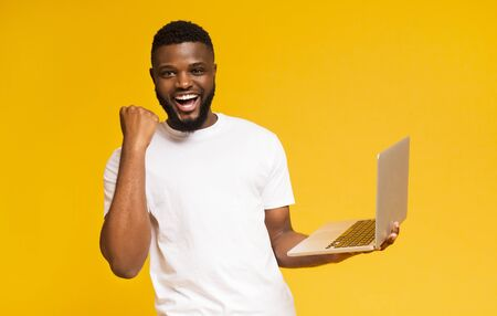 Happy black millennial guy celebrating win with laptop, shouting yes on yellow studio background