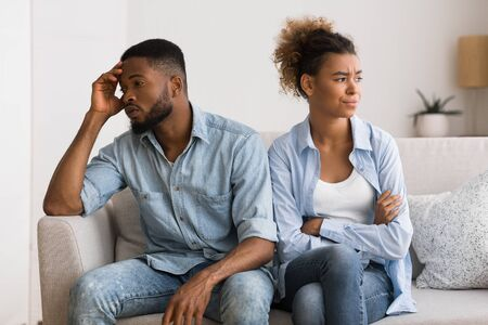 Misunderstanding In Relationship. Frustrated Black Man And Woman Avoiding Eye Contact Sitting On Couch At Home. Stock Photo