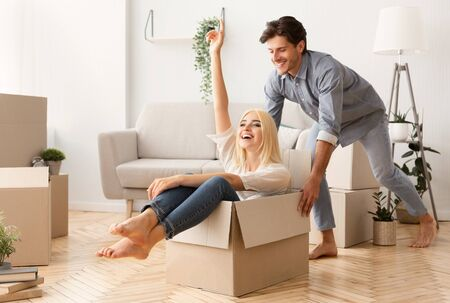 Moving New Apartment. Husband Having Fun Riding His Wife In Carton Box During Relocation Stock Photo