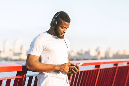 Young Black Jogger Setting Playlist On His Cellphone Before Exercising, staying on the bridge, free space Banco de Imagens