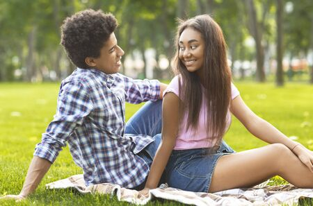 Happy teenage couple resting in park, looking at each other enjoying time together. Copy space