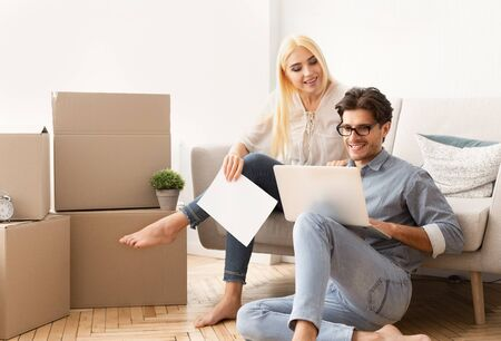 Buying and moving house. Happy couple relaxing on couch and reading certificate of property in new apartment. Copy space