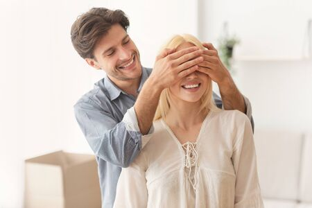 Welcome Home. Happy Man Covering Woman Eyes Before Showing Their New Apartment. Empty Space Stock Photo