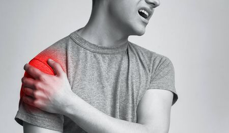 Muscle pain. Man with inflamed shoulder zone, monochrome photo