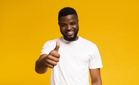 Recommend you. Happy black guy showing thumb up and smiling over yellow background