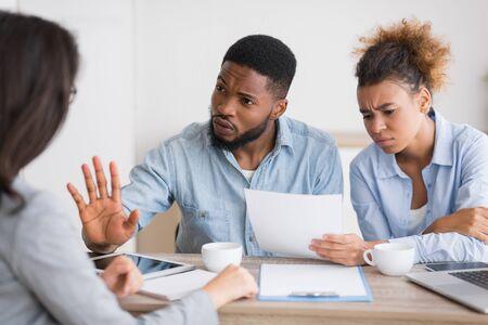 Coppia afro arrabbiata che critica e rifiuta i consigli dei broker assicurativi seduti nel suo ufficio. Messa a fuoco selettiva Archivio Fotografico