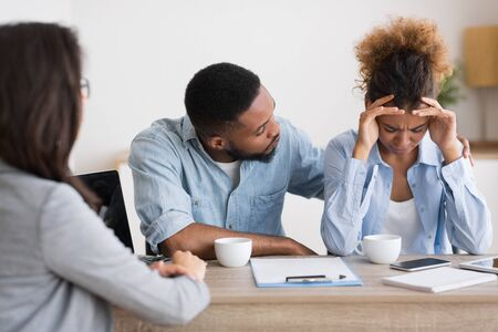 Afro Husband Comforting His Wife Crying On Family Or Adoption Counseling. Selective Focus