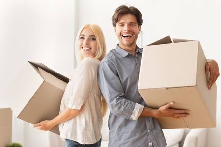 Joyful Couple Holding Boxes Ready For Moving New Apartment. Free Space For Text