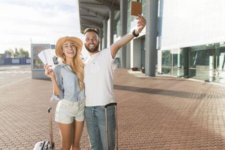 Travel concept. Loving couple going on vacation and holding tickets against airport building
