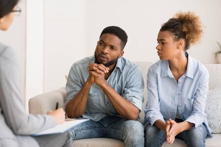 Marital Therapy. Black Couple Listening To Counselors Advice Sitting On Couch In Office.
