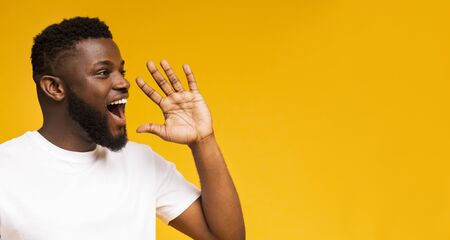 Attractive african guy shouting at copy space, making announcement, sharing news on yellow studio background. Panorama