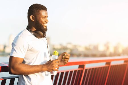 Smiling Afro Man Holding Bottle Of Water, staying on the bridge in sun lights, empty space