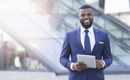 Best Business Apps. Smiling African American Businessman Holding Digital Tablet Standing In Urban Area. 写真素材