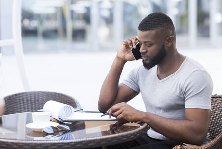 Serious african man checking financial plan data with collegues by phone, copy space