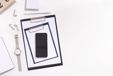 Creative composition. Cellphone with blank space and office supplies on white  with copy space