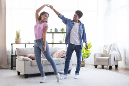 Romantic teen african american couple dancing at home enjoying weekend, guy holding girlfriends hand up, copy space