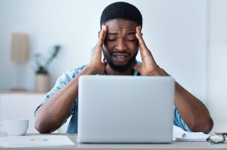 Tired afro businessman having headache at office, feeling sick while working on laptop. Stock Photo