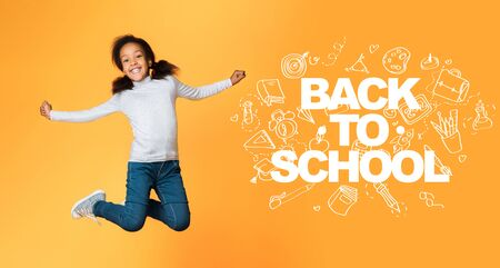 Back to school concept. Little girl child jumping, having fun over orange