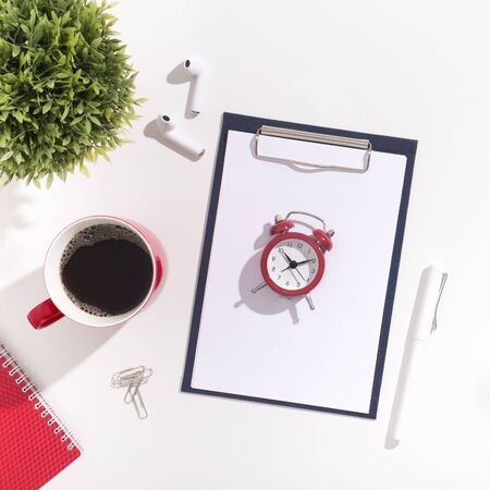 Alarm clock with red cup of coffee and earphones on white modern office table