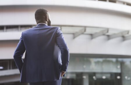 Rear view of unrecognizable confident black businessman in suit with his hands in pockets against modern office center