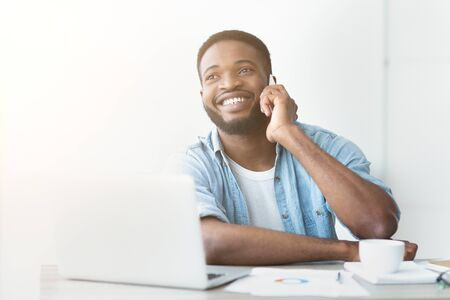 Satisfying call. Young black businessman talking on mobile phone and working on laptop in modern white office, copy space