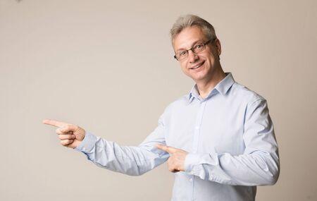 Happy senior man pointing away on grey studio