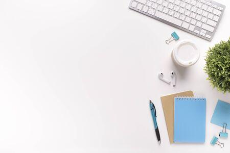 Minimalistische flache Lay-Komposition. Weißer Tisch mit Tastatur und Bürobedarf, Kopierraum für Werbung