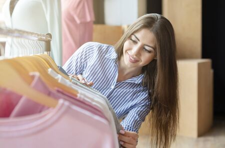 Excited Caucasian Girl Checking On Special Proposition At Clothing Store, empty space Stock Photo