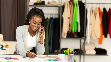 Clothing Store. Smiling Afro Girl Receiving Phone Order Of Designer Clothes In Boutique. Stock Photo