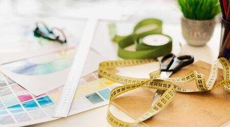 Fashion Design Background. Closeup Of Dressmakers Desk With Measuring Tape And Color Palettes. Selective Focus, Panorama, Copy Space Stock Photo