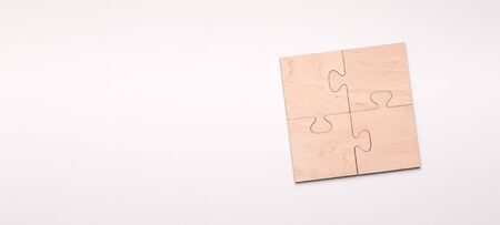 Puzzle of four wooden pieces with copy space for text Imagens