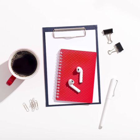 Red Cup of coffee, earphones and notebook on white office table