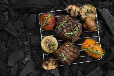 Flat lay of well done meat steak with vegetables on coals, copy space for text, black Imagens