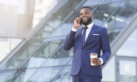 Successful Business Communication. Afro Businessman Speaking On Phone And Holding Coffee Cup Against Building In City. 写真素材