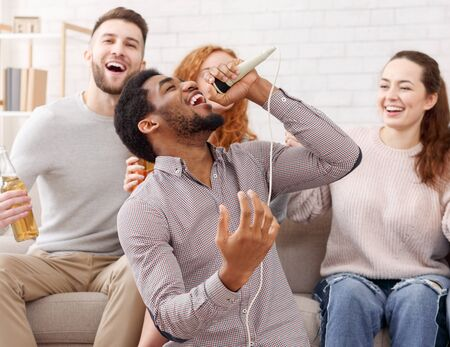 Young man holding microphone and singing at karaoke, having home party with friends Stock Photo