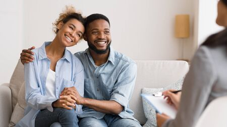 Afro Spouses In Love Hugging After Making Up Quarrel At Counselors Office. Stock Photo