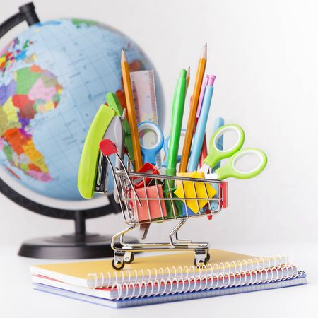 Back to school concept. World globe and shopping cart with stationery on white