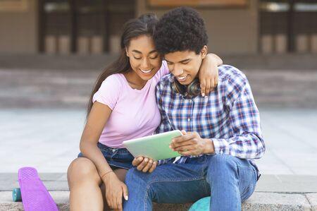 Dark-skinned teens watching funny video on digital tablet sitting outdoors, copy space 版權商用圖片