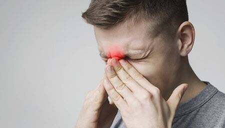 Seasonal virus. Stressed young man suffering from sore nose, free space Stock Photo