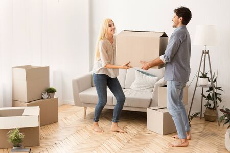 Glad Husband And Wife Carrying Box Into New Flat. Empty Space Stock Photo